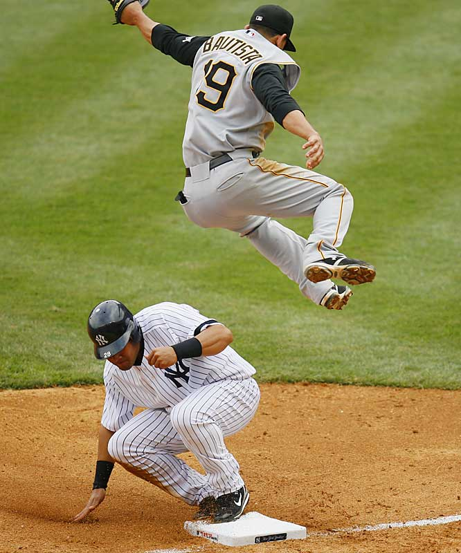Melky Cabrera slides safely into third on a double steal as Jose Bautista is drawn off the bag trying to catch a high throw during the sixth inning Saturday at Yankee Stadium. New York won 9-3.