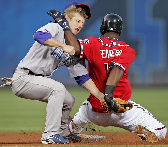 The Braves' Edgar Renteria smacks Cubs second baseman Mike Fontenot in the face while stealing second during the first inning Sunday at Turner Field. Renteria was retaliating to Cubs starter Ted Lilly hitting him with a pitch moments earlier, after which Lilly was ejected.