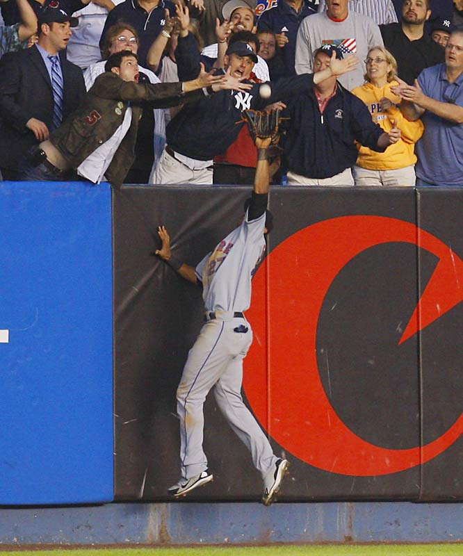 Mets leftfielder Carlos Gomez prevents a three-run homer by Miguel Cairo with a leaping catch above the wall near the outstretched arms of Yankee fans in the fourth inning June 15 at Yankee Stadium. Gomez then threw to second, easily doubling up Hideki Matsui.  The Mets won 2-0.