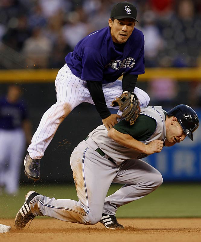 Rockies second baseman Kazuo Matsui lands on the Devil Rays' Brendan Harris after forcing him out and turning a double play with a throw to first in the seventh inning Saturday at Coors Field. Colorado won 10-5.