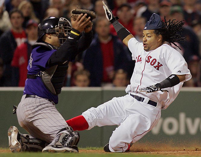 The Red Sox' Manny Ramirez slides safe at home as he beats the throw to Rockies catcher Yorvit Torrealba in the seventh inning June 14 at Fenway Park. Colorado won 7-1.