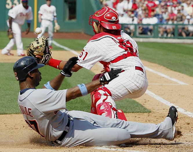 The Tigers' Craig Monroe slides past Phillies catcher Carlos Ruiz to score during a five-run seventh inning for Detroit on Sunday at Citizens Bank Park. The Tigers won 7-4.