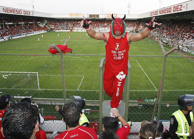 *El SuperDiablo* (The SuperDevil), a leader of Toluca's supporters group, *La Perra Brava*, rallies the home fans behind the goal during their team's 2-0 loss to Pachuca on April 15.  El SuperDiablo says he owns five different *Lucha Libre* masks that are common to the popular form of Mexican pro wrestling. This one includes devil horns and strings of tiny red-and-green ersatz sausages--a symbol of the *chorizos* that the city of Toluca is famous for.