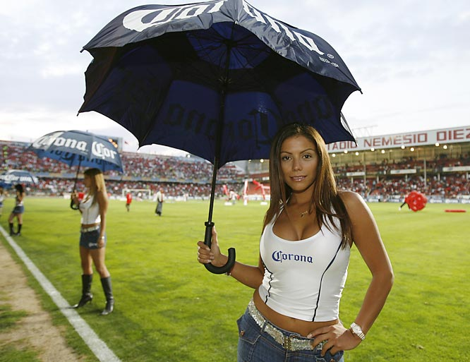 "One of the ever-present ""Corona girls"" poses under an umbrella at halftime of Pachuca's 2-0 win at Toluca on April 15. During postgame press conferences Corona girls will scurry to stand behind athletes being interviewed on-camera, the better to display themselves (and their brand names) to the masses."