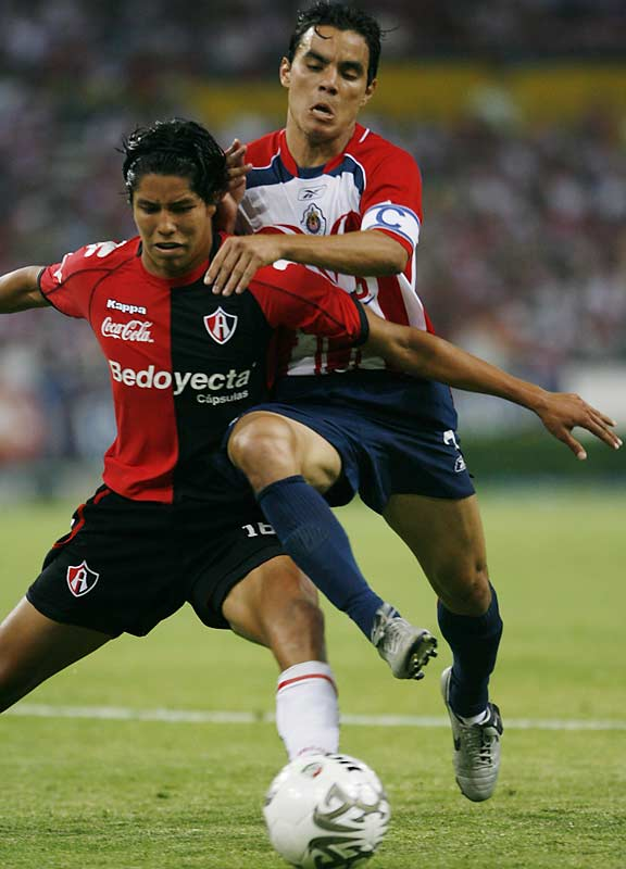 Chivas forward Omar Bravo battles with Atlas defender Hugo Ayala in a game that got chippy on several occasions.