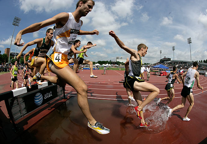 The steeplechase field negotiates the water jump.