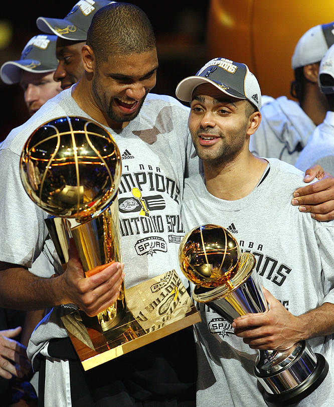 Tim Duncan cradles the Larry O'Brien trophy for the fourth time, while Tony Parker holds his Finals MVP hardware.