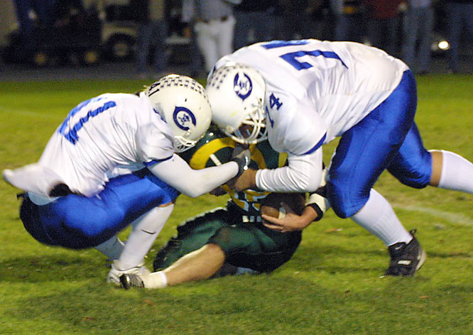Matt Smith (right) and Dan Thomasik of Oscar A. Carlson High in Michigan sack the QB from Flat Rock Community High.