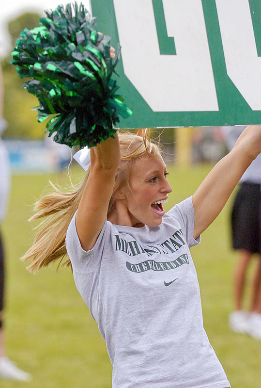 A smiling Michigan State cheerleader practices her sign holding.