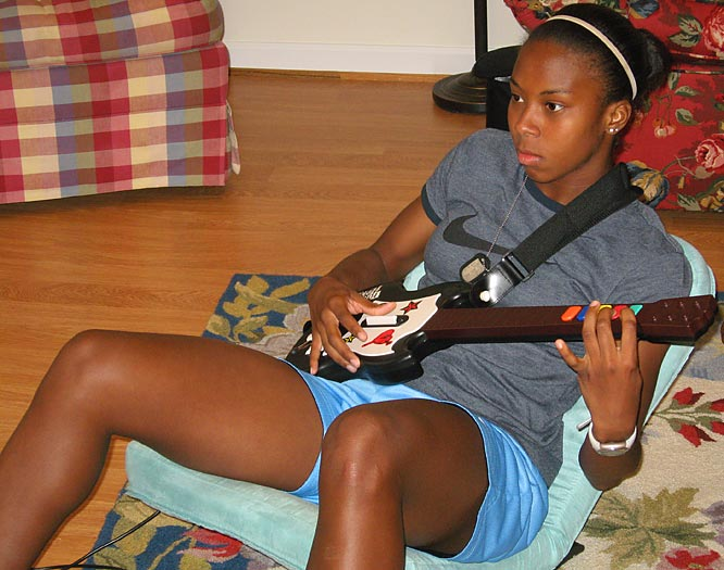 """Guitar Hero -- many have tried, few have mastered it.  While spectators of Washington have yet to declare her a legend, she certainly looks the part.  Just as she is entertained with a guitar, her roommates are entertained waiting for her """"Kiss tongue"""" to poke through when she becomes completely absorbed in her, err, music."""