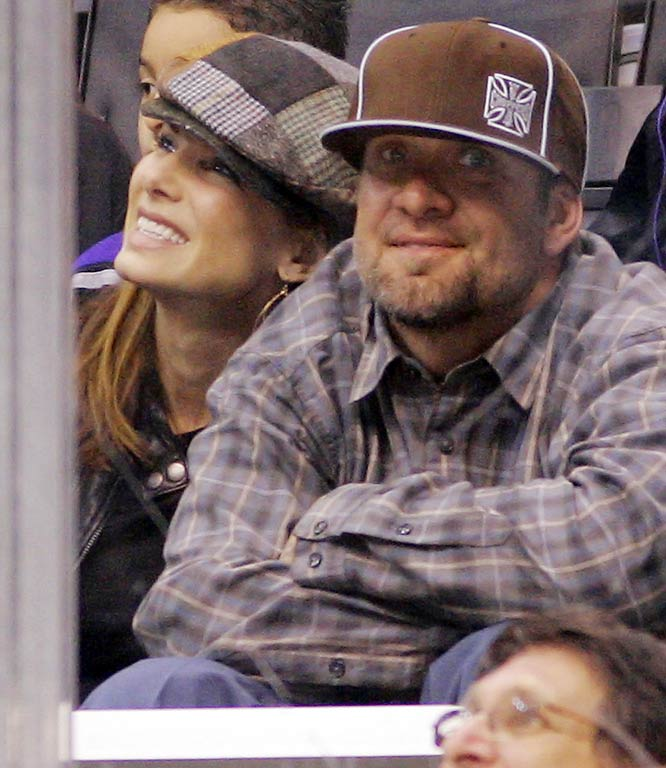 Sandra Bullock, with husband, Jesse James at this past week's Ducks-Kings game, looks way too happy to be watching exhibition hockey.