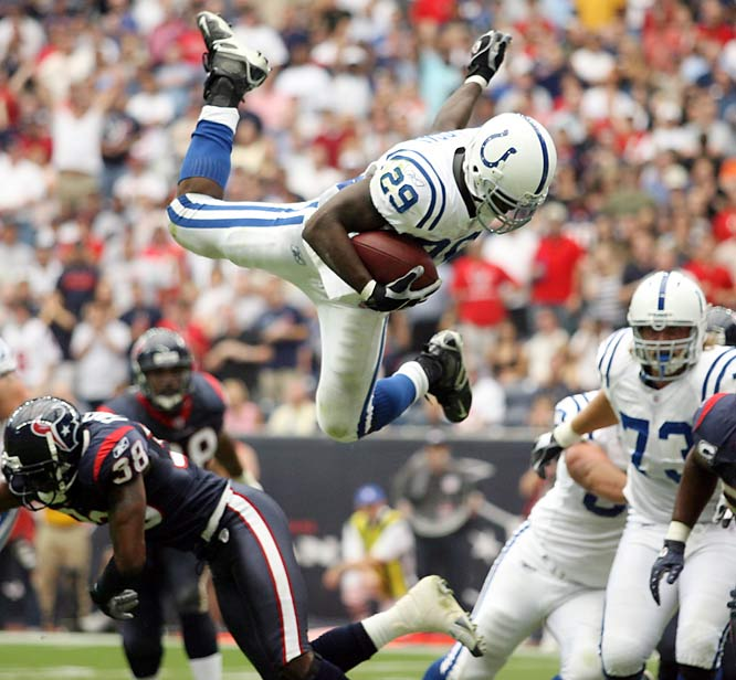 Joseph Addai leaps over cornerback Demarcus Faggins for a touchdown in the second quarter. Addai scored twice against the injury-riddled Texans, who were without star receiver Andre Johnson and lost players throughout the game, including running back Ahman Green to a knee injury.