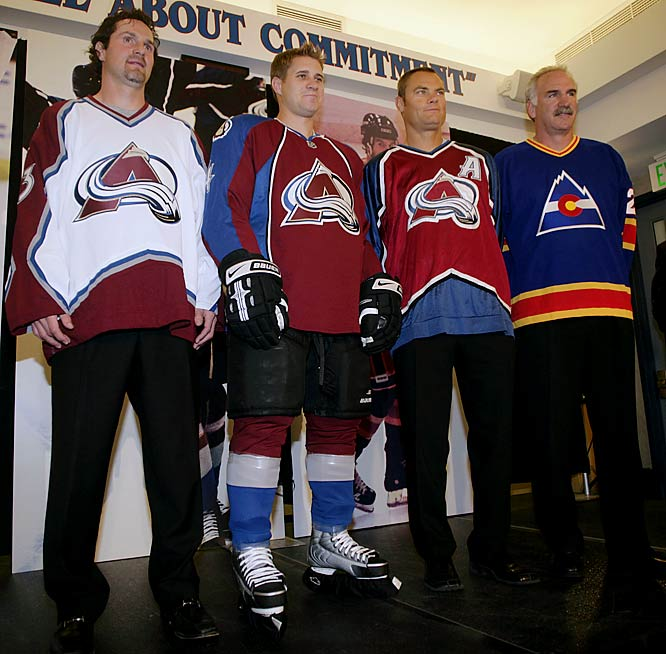 Colorado's hockey history on display: Avalanche defenseman John-Michael Liles (second from left) wears the team's new uniform. Former defenseman Curtis Leschyshyn (third from left) is in their original jersey from 1995. Coach Joel Quenneville displays the sweater of Colorado's first NHL team: the Rockies, now the New Jersey Devils.