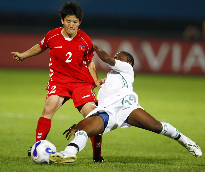 Korea DPR's Kim Kyong Hwa holds off Nigeria's Lilian Cole.  Korea won the match 2-0.