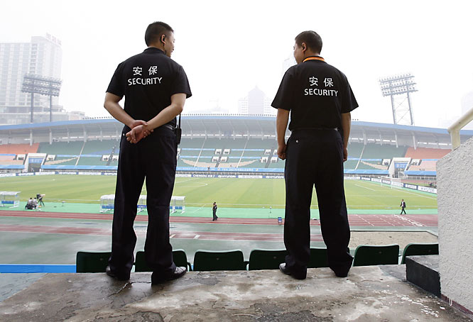 Security guards in Chengdu, China look over Sports Center Stadium prior to the action.