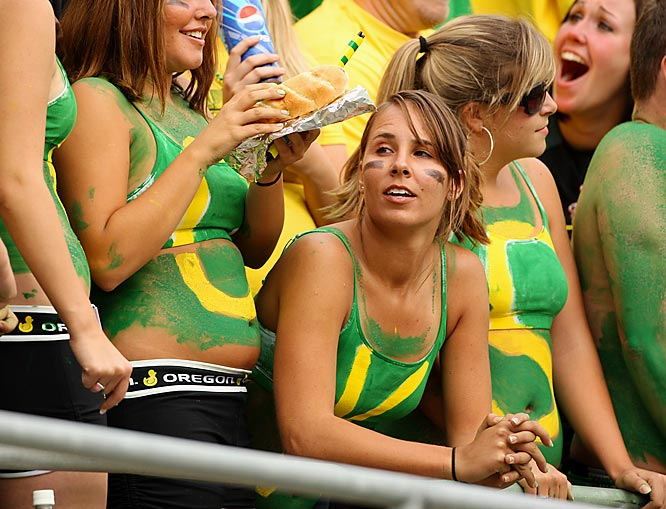 An Oregon fan watches the action ... while her friend devours a sub.