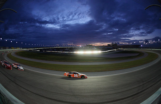 NASCAR's season finale in Homestead,  when Tony Stewart won the second championship of his career. As the sun set over the track, the sky developed into a wonderful setting coupled with the lights of the track. I wanted to illustrate that sense in the picture as the #20 car was in the turn.  Using a fisheye lens, I made a picture that highlighted the car, yet showed the dramatic sky at sunset.<br><br>Shot with: Canon EOS-5D, EF 15mm f/2.8 fisheye, shot at 1/1600 f/2.8.