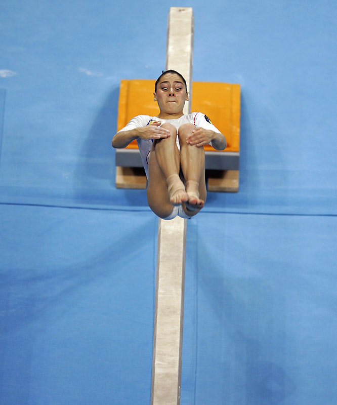I always look for unique angles that can illustrate a graphical look. At the 2004 Summer Olympics in Athens, I found an upper area above the balance beam.  I made this picture as Oana Ban of Romania backflipped during her routine.  I was fortunate enough to make this picture, dramatically showing the strength and grace of this athlete.<br><br>Shot with: Canon EOS-1D Mark II, EF 400mm f/2.8L IS USM, shot at 1/1000 f/2.8