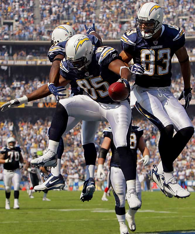 Tight end Antonio Gates celebrates his 49-yard touchdown reception with teammates LaDainian Tomlinson and Vincent Jackson, right, in the first quarter. Gates scored twice as the Chargers dominated the Texans just two days after the last wildfire evacuees left Qualcomm Stadium.