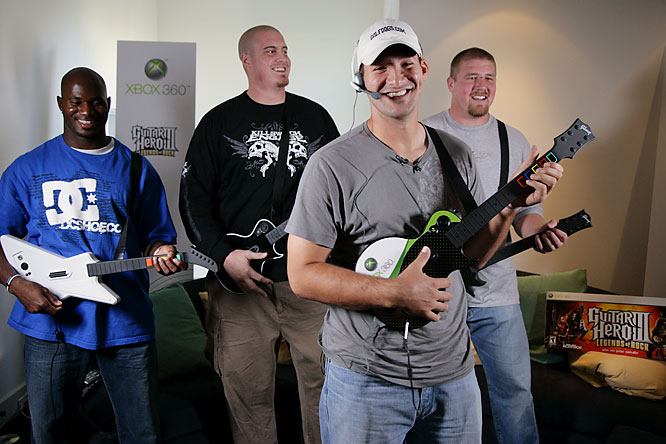 Dallas Cowboy Tony Romo acts as lead singer while he plays Guitar Hero III with his teammates Terrance Newman, Marc Colombo and Cory Procter.