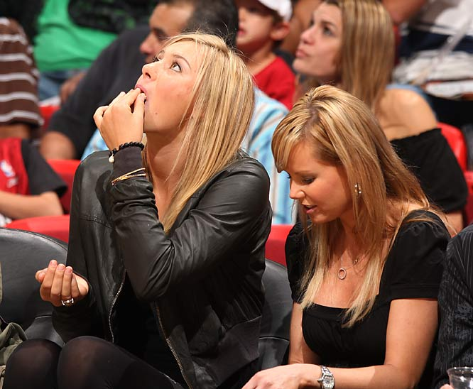 Maria Sharapova multitasks by eating popcorn and checking the scoreboard at a Celtics-Heat game.