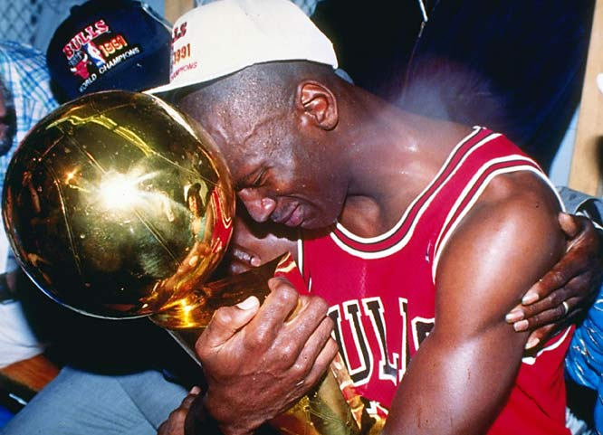 Michael Jordan hugs his first championship trophy after the Bulls defeated the Lakers in the NBA Finals.