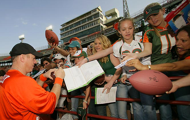 Former Miami quarterback Jim Kelly signs autographs for fans after the final game at the Orange Bowl -- a flag football contest between former Hurricanes and Dolphins.