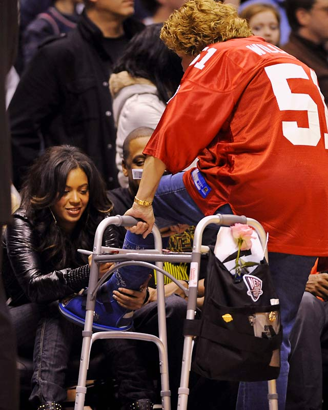 Beyonce proves to be a good sport as she signs a fan's cast during Wednesday's Nets game. How long before that cast is on eBay?