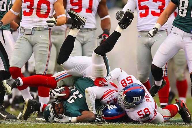Michael Johnson and Antonio Pierce tackling Eagles' running back Brian Westbrook.