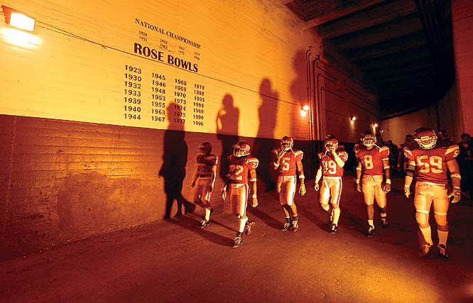 """The Los Angeles Coliseum is steeped in history. The players must walk down a long, large tunnel from the bowels of this 1932 landmark to reach the playing field. The records of the USC national championship and Rose Bowl teams used to be hand painted up on the wall of that tunnel. Led by Reggie Bush (No. 5), this Trojan squad would march past those noted teams before every home game and make their own mark in Trojan lore. They would go on to beat Michigan in the Rose Bowl and win a share of the national title. Alas, a proud Coliseum employee would not paint that team's """"name"""" up on the wall. A gaudy plastic coated banner has taken its place. Knowing that these Trojans were destined for greatness, I lit this piece with one low strobe covered with a golden gel, which cast the larger than life shadows of the warriors upon the ancient wall."""