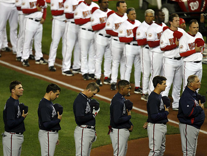 The Nationals and Braves remove their caps for the National Anthem and await the start of a brand new season.