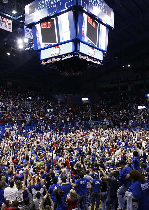 Kansas fans celebrate on the floor of Allen Fieldhouse after the Jayhawks won the NCAA basketball championship.