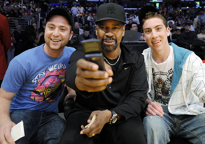 Denzel Washington gave a couple of fans a thrill by taking a picture with them at Tuesday's Kings-Lakers game.