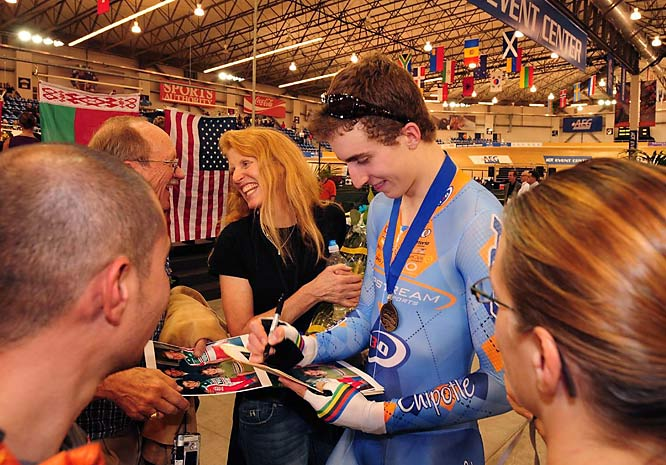 Connie Carpenter-Phinney watches her son, Taylor, sign autographs as he follows in her footsteps to becoming another cycling champion.