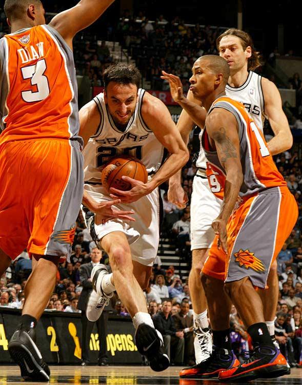 San Antonio's Manu Ginobili slips through a pair of Phoenix defenders.