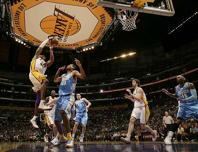 Kobe Bryant looks to pass over Marcus Camby.