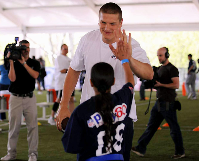 Top-pick Jake Long high-fives a participant in the Youth Clinic.