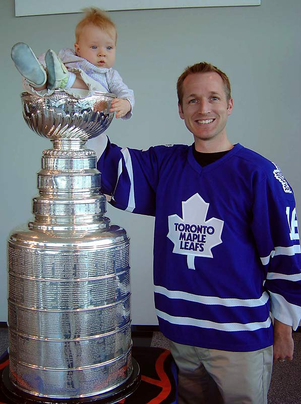 """""""This picture of my daughter and I was taken 3 years ago at a charity event in my office building.  When the cup arrived I asked half jokingly to the assistant if he'd let me put my baby girl in the cup.  He said 'sure, no problem'.  So I had to call my wife to drop what she was doing and bring Madelyn and my Leafs jersey to work! """" -- Colin Brown"""