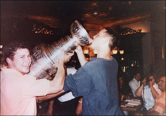 """Here's a photo of Robb Brady and Mark Sather (drinking), and the Stanley Cup. This was taken after Calgary won the Cup and was taken at the Broadmoor hotel in Colorado Springs, Colo. I asked Mrs. Bob Johnson if I could take a picture of the Stanley Cup. She responded: """"You cannot take a picture of the Stanley Cup. However you may take a picture of you drinking beer from the Stanley Cup."""" -- Mark Sather"""
