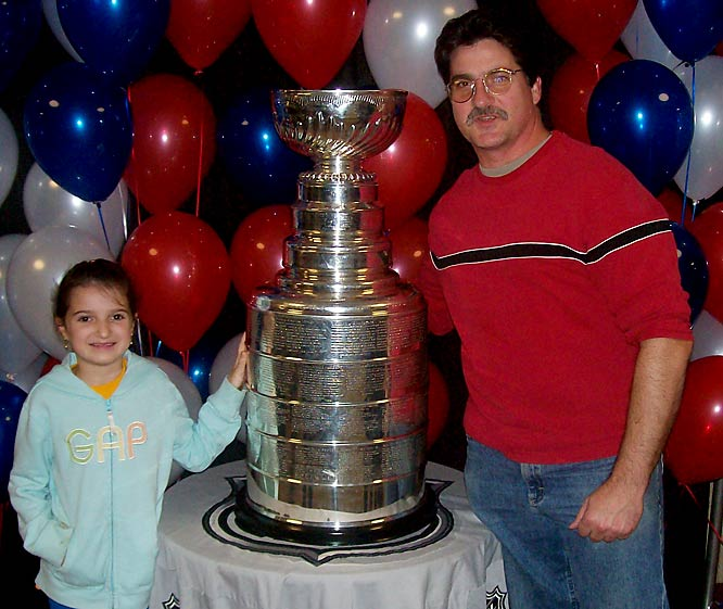 """""""This picture was taken during a Ranger/Islander Game at MSG.  We didn't know the Cup would be there and I asked my 7 year old if she wanted to see the Cup.  Wise girl that she is, she said yes.  We waited for almost the entire 2nd Period.  Fortunately someone on the line (who I happened to play roller hockey against) had a cell phone camera or all I would have had was a lousy Polaroid."""" -- John Tipaldo with daughter Allison"""