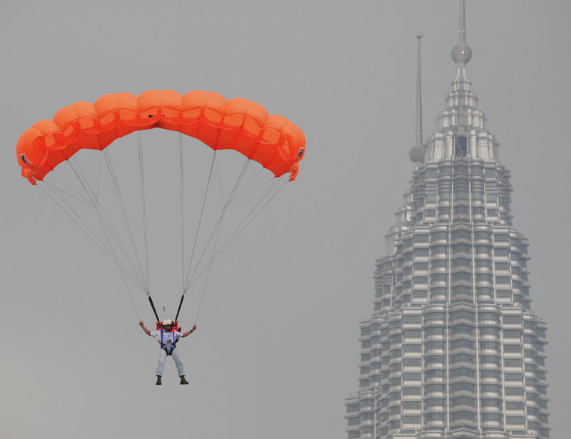Small, isolated protests marred the flame's tour through the country, but other attractions in Malaysia included this parachutist who jumped from a TV tower.