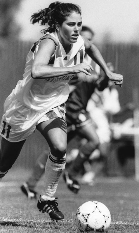 A four-time NSCAA All-America midfielder, Julie Foudy was the 1989 Soccer America Freshman of the Year and 1991 Player of the Year. She finished her Stanford career with 52 goals, 32 assists and 136 points. She played on the Women's USA National Team for seventeen years, scoring 45 goals and making 271 appearances. She won an Olympic gold medal in 1996 and was captain of the team in 2000 and 2004 when they won a silver and gold medal, respectively.