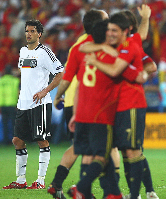 Spanish players celebrate as Michael Ballack, who once again came up empty in a championship, looks on.