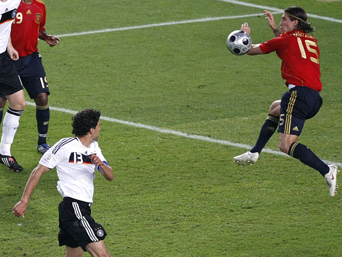 A shot by Germany's Michael Ballack glances off the arm of Spain's Sergio Ramos.