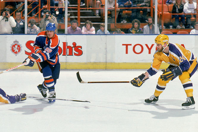 """Huge favorites against a team with a 24-41-15 regular-season record, Wayne Gretzky's high-powered Oilers grabbed a 5-0 lead after two periods in Los Angeles and looked like a lock to take a two-games-to-one lead in the best-of-five series. But Jay Wells (right) scored for the Kings at 2:46 of the third period and the rally continued with a power play tally by Doug Smith, a freak goal by Charlie Simmer that was knocked into the net by Oiler goalie Grant Fuhr, and a four-on-four score by Mark Hardy. With only five seconds left, Steve Bozek pounced on a rebound and backhanded it home to force overtime. The Kings won """"The Miracle on Manchester"""" -- so named for the street on which LA's Great Western Forum stood -- at 2:35 of the extra frame when rookie winger Daryl Evans blasted a slapper past Fuhr. The Kings went on to win the series, too."""