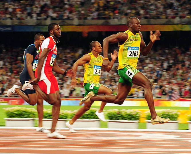 Jamaica's Usain Bolt breaking his own world record in the 100 meters, running the race in 9.69 seconds despite visibly slowing down to celebrate before crossing the finish line.