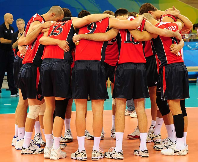 The U.S. men's volleyball team huddling in a moment of silence before their first game without coach Hugh McCutcheon, whose father-in-law had been stabbed to death at a popular Beijing tourist site. The team would rally in the wake of tragedy, winning a gold.