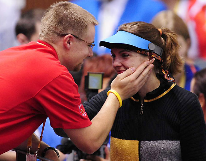 Czech Republic's Katerina Emmons is congratulated by her husband Matt of the U.S.after winning the first gold medal of the games, in the 10 meter air rifle.