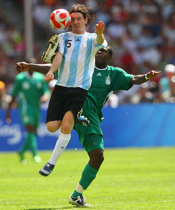 Argentinean soccer sensation Lionel Messi  goes airborne to win the ball from Chibuzor Okonkwo of Nigeria.