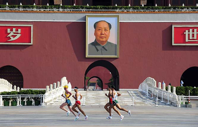 Marathon runners pass the portrait of chairman Mao on Tiananmen Square during the final day of the Beijing Games.